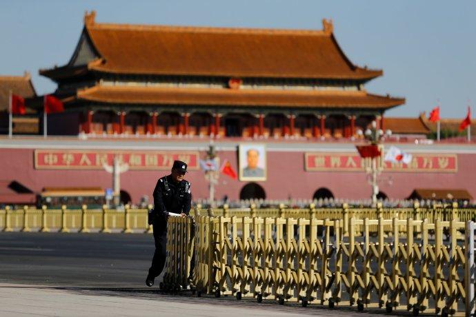 Čínský policista sklízí bezpečnostní zábrany na pekingském náměstí Nebeského klidu (Tchien-an-men), říjen 2018. Foto:Thomas Peter, Reuters