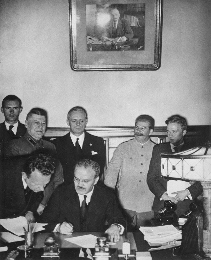Podpis druhého tajného dodatku Smlouvy oneútočení mezi Německem aSovětským svazem, přezdívané pakt Molotov–Ribbentrop, vmoskevském Kremlu 28.září 1939(Smlouva aprvní tajný dodatek rozdělující východní Evropu mezi Německo aSSSR byly podepsány 23.srpna 1939). Hitlerův ministr zahraničí Joachim von Ribbentrop stojí třetí zleva, vedle něj je Josif Vissarionovič Stalin. Sovětský ministr (lidový komisař) zahraničí Vjačeslav Molotov dokument podepisuje. Foto:Autor neznámý, NARA.gov