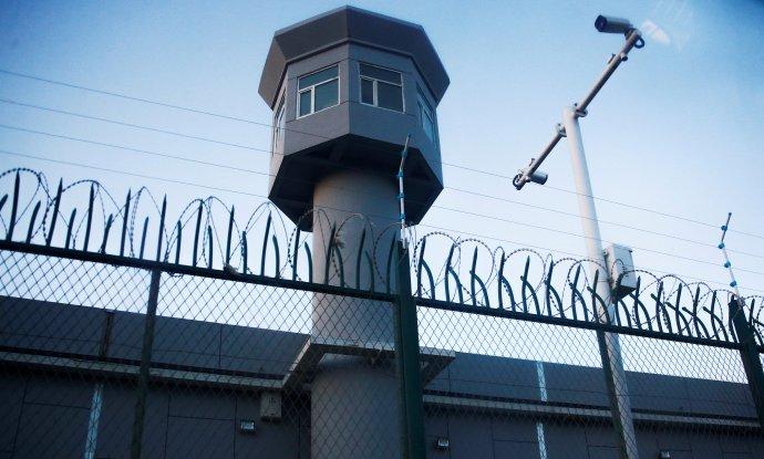"""Ostnatý drát, strážní věž, bezpečnostní kamery: """"středisko odborné výchovy"""" ve čtvrti Ta-ban-čcheng v Urumči, hlavním městě Sin-ťiangu. Patří mezi největší koncentrační tábor v Číně. Snímek je ze září 2018 a jeho autory pak hodiny zadržovala police. Foto: Thomas Peter, Reuters"""