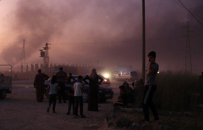 Lidé zpovzdálí sledují zkázu arabsko-kurdského města Ras al- Ajn na syrsko-tureckých hranicích, ze kterého utekli před tureckou invazí. Foto: Rodi Saíd, Reuters