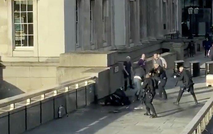 """Policejní jednotka na London bridge zasahuje proti Usmanu Khanovi, který v Londýně pobodal několik lidí. Krátce po tomto momentu ho zastřelí. Foto z videa zveřejněho na Twitteru uživatelem """"Hand luggage only"""", Reuters"""