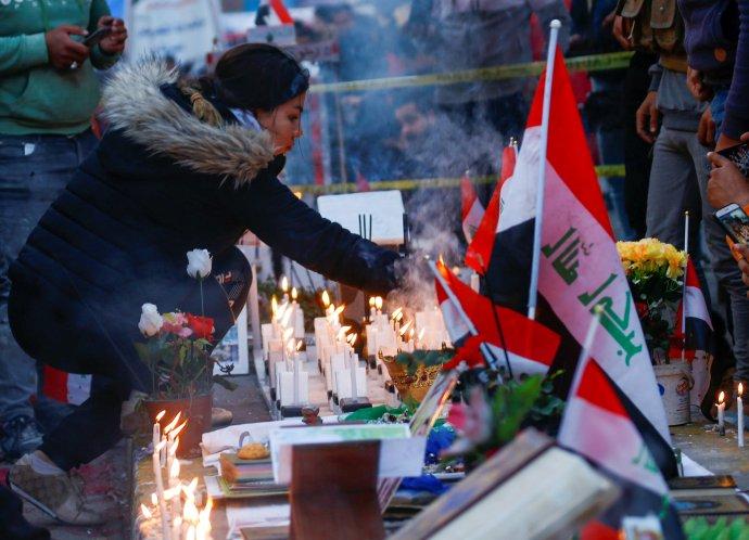 Irácká demonstrantka zapaluje v iráckém Bagdádu svíčku za lidi zabité během protivládních protestů. Foto: Alá al-Mardžání, Reuters