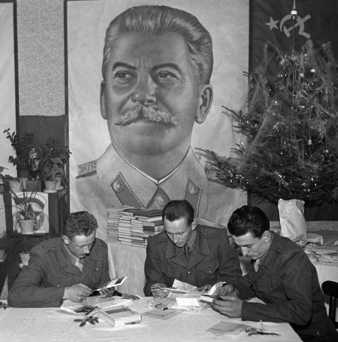 """Dobový popisek agentury ČTK z roku 1950: Letošní Štědrý den byl opravdu šťastným, radostným a bohatým pro ty, kteří jej prožívali v kruhu svých velitelů a zástupců pracujícího lidu u vojenských útvarů. Ti, kteří právě neměli službu, sešli se na Štědrý den ve vyzdobené jídelně se svými veliteli, politickým pracovníkem, zástupci pracujícího lidu patronátního závodu, zástupci lidosprávy, s chlapci a děvčaty z ČSM a pionýry národní školy, kteří v soudružském kolektivu, pevně spjati s myšlenkou bránit a uhájit mír, společně s vojáky prožívají Štědrý večer. Na snímku si vojáci si rozbalují dárky (za nimi velký obraz J. V. Stalina)"""". Foto: ČTK"""