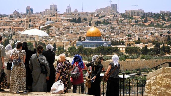 Křesťanský ortodoxní průvodce ukazuje zOlivové hory turistům Jeruzalémské staré město. Foto:kirill4mula, Adobe Stock