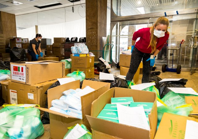 Krabice se zabavenými respirátory. Na nerozbalené krabici vlevo je vidět čínská a italská vlajka. Foto: ČTK