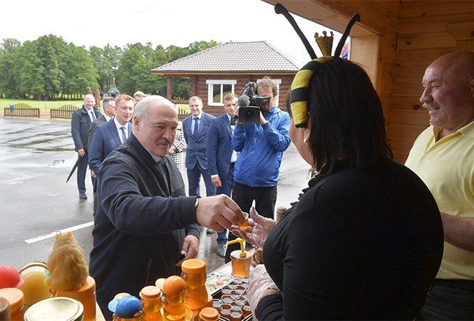 Běloruský prezident Alexandr Lukašenko si zakládá na svém lidovém vystupování a projevu. Tentokrát si připíjí s producentkou medu v kostýmu včelky. Zdroj: president.gov.by