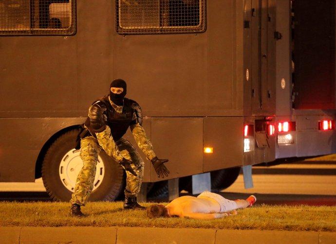Příslušník speciálních běloruských jednotek OMON nad tělem muže, kterého srazilo vnoci na pondělí vcentru Minsku policejní vozidlo. Foto:Reuters / Vasilij Fedosenko