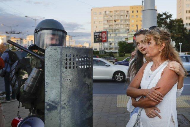 Ženy vcentru Minsku spříslušníkem policie. Foto:Sergej Grits, AP Photo