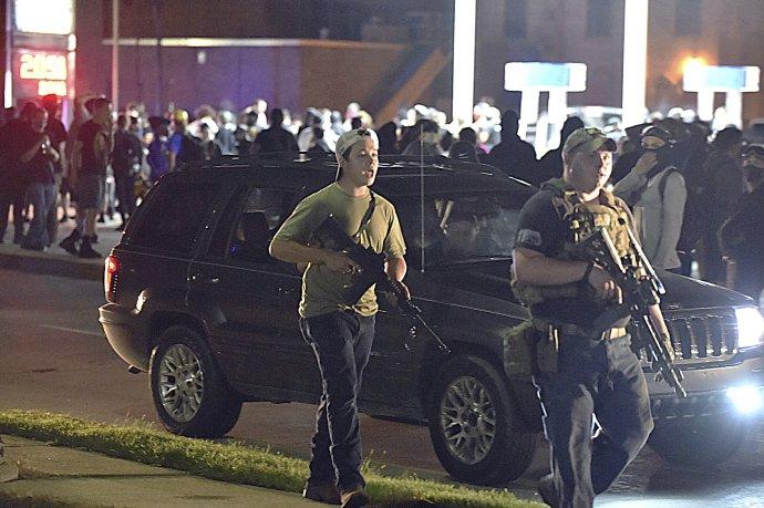 Kyle Rittenhouse (vlevo) prochází spolu sdalším ozbrojeným civilistou ulicí města Kenosha krátce předtím, než zastřelil dva muže adalšího zranil. Foto:ČTK / The Journal Times via AP