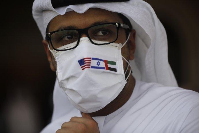 Člověk v tradičním arabském oděvu doplněném izraelskou a americkou vlajkou není na Blízkém východě často k vidění. Navázání leteckého spojení mezi Tel Avivem a Abú Dhabí to změnilo. Foto: ČTK/AP