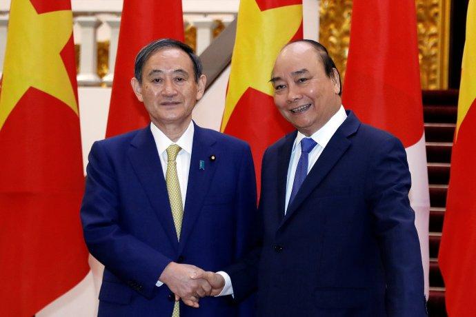 Japonský premiér Jošihide Suga (vlevo) si třese rukou s vietnamským protějškem Nguyen Xuan Phucem. Tokio s Hanojí uzavřelo dohodu o bezpečnostní spolupráci. Foto: Luong Thai Linh, Reuters