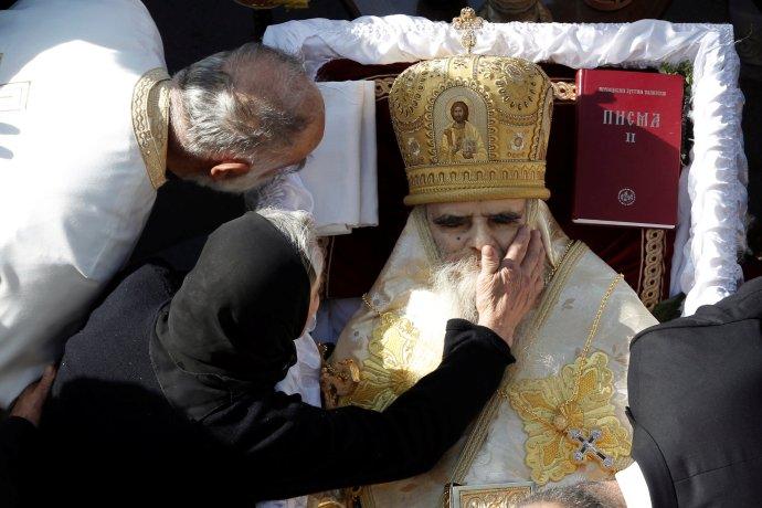 Věřící se dotýkají mrtvého těla metropolity Amfilohije, hlavy Srbské pravoslavné církve vČerné Hoře, který zemřel na covid. Pohřeb se konal vhlavním městě Podgorica 1.listopadu avedl ho patriarcha Irinej. Ten zemřel minulý pátek. Foto:Stevo Vasiljević, Reuters