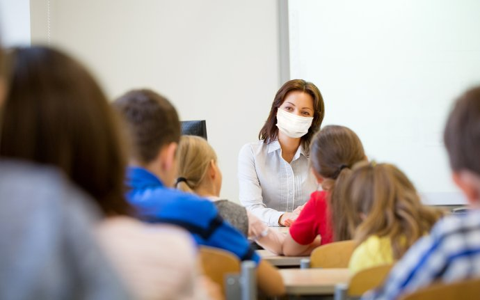 education, school and pandemic concept - teacher wearing face protective medical mask for protection from virus disease teaching group of students in classroom