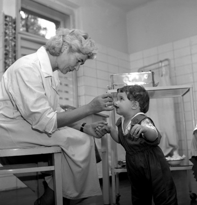 """""""Vtýdnu od 27.května do 1.června probíhá na celém území naší republiky druhá etapa očkování proti dětské obrně živou očkovací látkou. Na sn. záběr zdětského zdravotnického střediska vPraze6-Vokovicích."""" Foto adobový text zroku 1960: ČTK"""