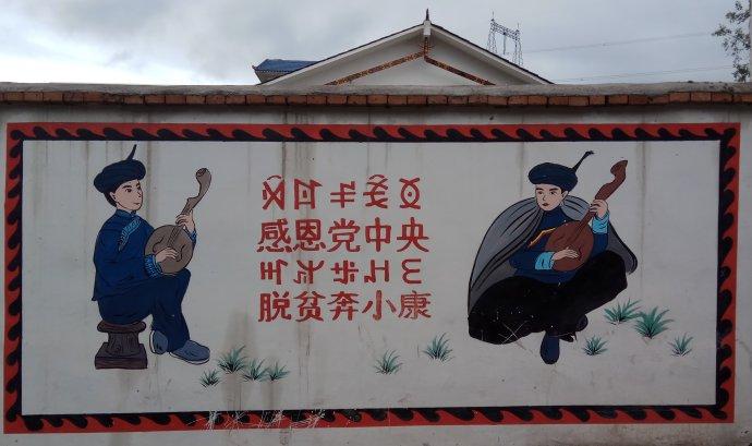 """""""Ústřednímu výboru Komunistické strany Číny patří vděčnost za odstranění chudoby aúprk vstříc společnosti mírného blahobytu."""" Nuosusko-čínský propagandistický nápis velké kampaně proti chudobě na zdi unového domu vIské samosprávné prefektuře Liang-šan. Obrázek má znázorňovat tradiční kulturu místní národnostní menšiny. Foto:Jan Karlach"""