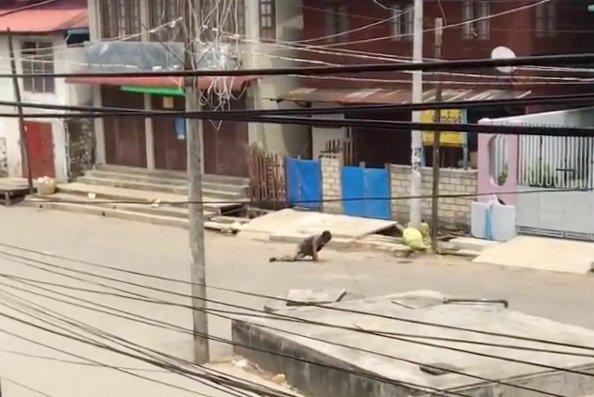 """Muž se po kolenou plazí zaprášenou prázdnou ulicí. Snímek je rozmazaný, ale itak jde rozpoznat, jak se muž namáhavě opírá opravou ruku, jak pospíchá, přestože na to nemá sílu. Aktomu mrazivý popisek Reuters: """"Postřelený muž se snaží uprchnout bezpečnostním jednotkám, Mogok, Myanmar, 17.dubna 2021."""" Zdroj: Reuters"""