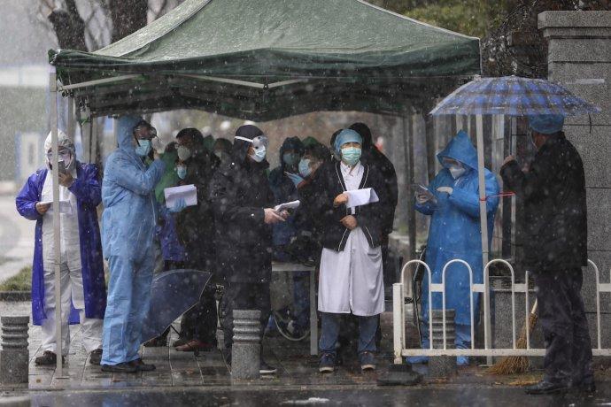 Před onkologickou klinikou ve Wu-chanu, nouzově předělanou na covidovou nemocnici, čekají 15. února 2020 zdravotníci a úředníci na pacienty. Foto: ČTK