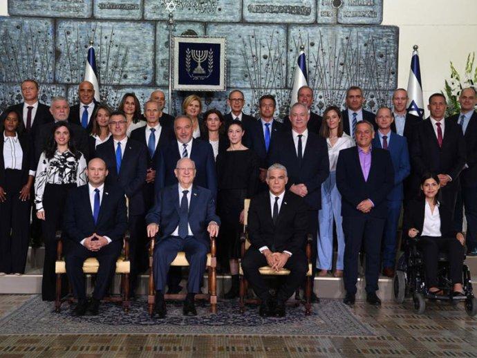 """Nová, postnetanjahuovská izraelská vláda skončícím prezidentem Rivlinem vkřesle uprostřed. Vlevo od něj premiér Bennett, vpravo ministr zahraničí ajeho předpokládaný nástupce Lapid. Vprvní řadě zcela vlevo ministryně vnitra Ajelet Šakedová, vedle ní ministr spravedlnosti Gideon Sa'ar avedle něj, za prezidentem, ministr financí Avigdor Lieberman. Za Lapidem ministr obrany Benny Ganc. Zarabské strany Ra'am, která je součástí koalice, je součástí vlády jen lídr Ra'am Mansúr Abbás, ale je """"jen"""" náměstkem pro arabské záležitosti vúřadu premiéra, proto na fotce ministrů není. Foto:izraelská vláda, Avi Ohaion, GPO"""