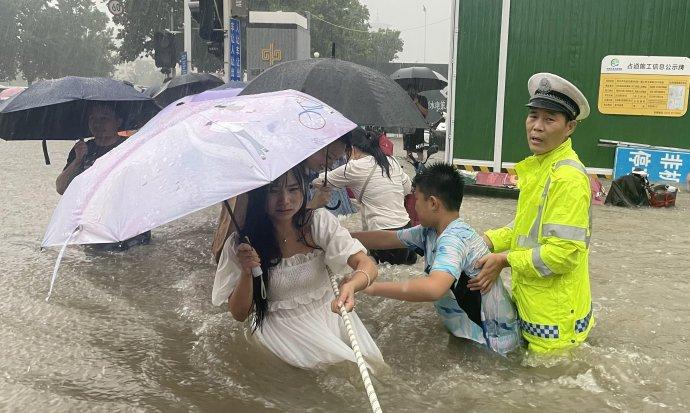 Ulice vdvanáctimilionovém Čeng-čou, úterý 20.července. Přívalový déšť neustává adopravní policista se snaží lidem pomoci přejít přes zaplavenou ulici. Foto:Reuters
