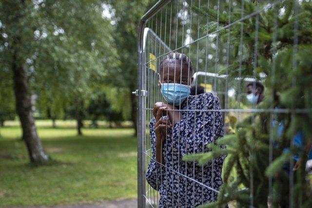 Neosanhare Esone Queenová, běženkyně zNigérie, vyhlíží skrze plot uprchlického tábora vLitvě. Foto:Mindaugas Kulbis, AP via ČTK