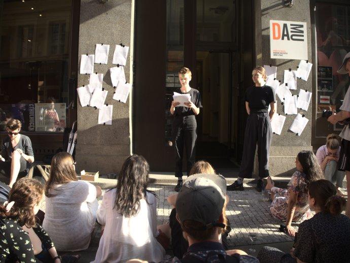 Členka iniciativy Ne!musíš to vydržet čte před vchodem DAMU příběhy svých spolužaček a spolužáků. Foto: Ne!musíš to vydržet
