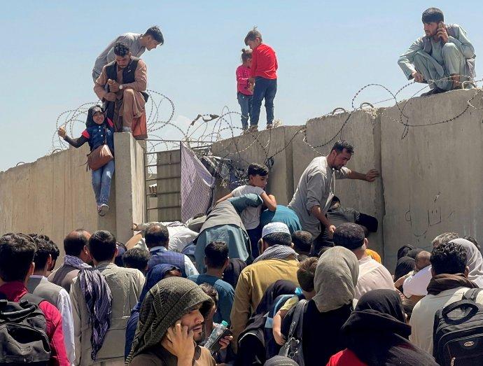 Zoufalí lidé se tlačí před zdí kolem letiště v Kábulu. Mladík vlevo se snaží vytáhnout malou dívku nahoru: tak, aby se oba dostali dovnitř, do areálu letiště. Foto: Reuters