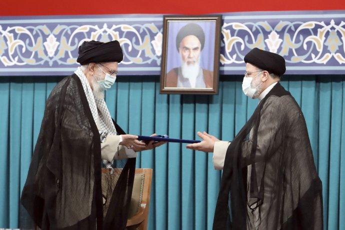 Výběr Raísího (na snímku vpravo) do prezidentského úřadu vúterý oficiálně potvrdil nejvyšší duchovní vůdce země ajatolláh Alí Chameneí (vlevo) za přísného dohledu otce íránské revoluce, ajatolláha Chomejního (portrét). Foto:ČTK/AP