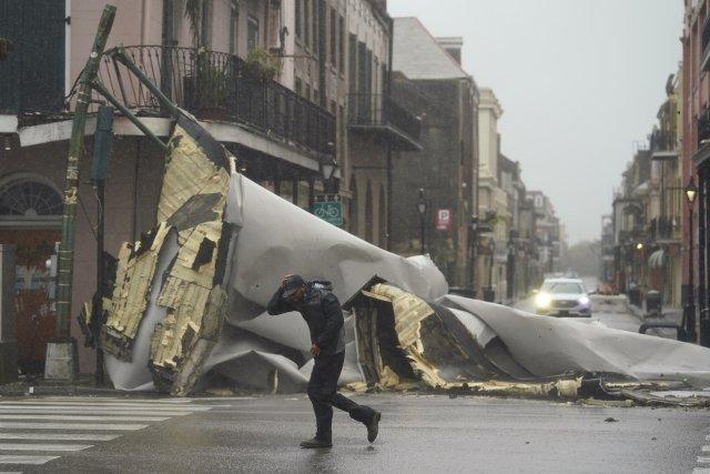 Muž prochází ve městě New Orleans kolem domu ve čtvrti French Quarter, kterému hurikán Ida odfoukl střechu. Foto: Eric Gay, AP/ČTK