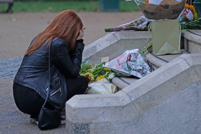 Žena pokládá květiny vlondýnském parku Clapham Common nedaleko od místa, kde byla naposledy spatřena Sarah Everardová živá. Březnové smuteční shromáždění policie na tomto místě sodvoláním na proticovidová opatření rozehnala, avyvolala tak uveřejnosti bouře nevole. Foto:ČTK/AP