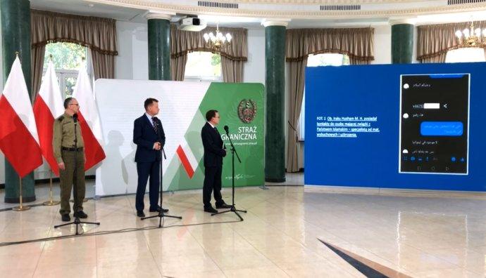 Polští ministři vnitra Kamiński (první zprava) a obrany Błaszczak ukazují médiím fotografie údajně nalezené v mobilech migrantů. Foto: repro z videa polského ministerstva vnitra